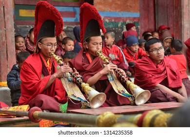 LO-MANTANG, NEPAL - MAY 14, 2018: Young monks perform religious music on ancient pipes during the Tiji festival in the capital of Lo Mantang kingdom of Mustang, Nepal.
