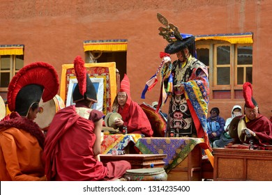LO-MANTANG, NEPAL - MAY 14, 2018 : Monk in mask performs the religious rite of secrecy of Tibetan Buddhism in front of the monks during the Tiji festival in capital of the kingdom of Mustang, Nepal