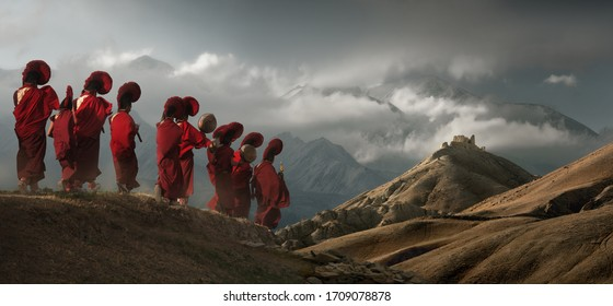 LO-MANTANG, NEPAL - MAY 16, 2018: Young monks in traditional clothes walk against background of the mountains to an old temple in the kingdom of Mustang, Nepal.