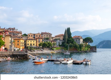 LOMBARDY, ITALY - AUGUST 03, 2018: Varenna port at sunset with people having fun on shore