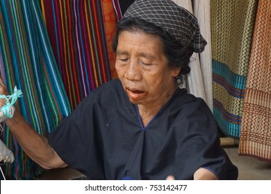 Lombok, Indonesia, 12 November 2017 -  Old woman works on traditional wooden weaving thread machine