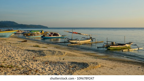 Lombok, Indonesia - Apr 17, 2016. Traditional boats waiting on the sea at sunset in Lombok, Indonesia.