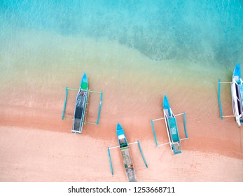 LOMBOK INDONESIA, DECEMBER 10 2018 : Aerial Pink Beach Lombok with traditional Boats. pink sand beach