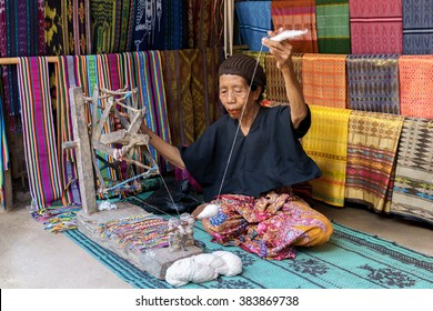 LOMBOK, INDONESIA - FEBRUARY 23, 2016: Sasak lady traditionally makes yarn with a spindle wheel at traditional Sasak village, Desa Sasak Sade, Lombok Indonesia.