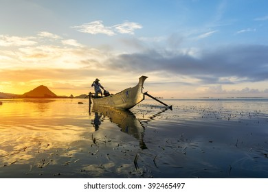 LOMBOK, INDONESIA - FEBRUARY 23, 2016: Unidentified fisherman with his boat during sunrise at Kuta, Lombok, Indonesia. (Image may contain noise,soft and blurry effect due to long exposure)