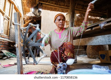 Lombok, Indonesia - July 20 2018: - Sasak lady traditionally makes yarn with a spindle wheel at traditional Sasak village, Desa Sasak Sade, Lombok Indonesia.