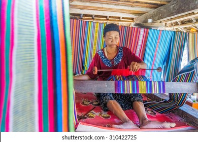 LOMBOK, INDONESIA - JUNE 5 : An elderly weave songket (traditional colorful fabric) using the classic loom on June 5, 2015 in Sade,Lombok. Sade village is famous for their beautiful cloth