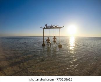 LOMBOK , INDONESIA - May 22, 2017: Beautiful Gate with a couple swinging above ocean sunset at Gili Trawangan island, Lombok, Indonesia.