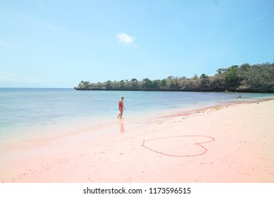 LOMBOK INDONESIA, September 7, 2018 : Beautiful woman in red bikini walking on pink beach Lombok