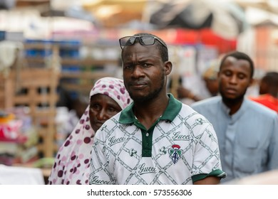 LOME, TOGO - Jan 9, 2017: Unidentified Togolese man wears sunglasses and Gucci shirt at the Lome central market. Togo people suffer of poverty due to the bad economy