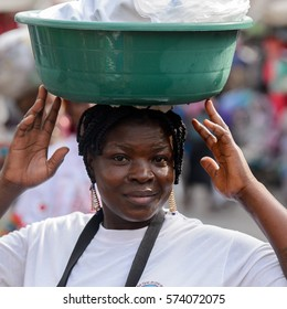 LOME, TOGO - Jan 9, 2017: Unidentified Togolese woman carries a basin on her head at the Lome central market. Togo people suffer of poverty due to the bad economy