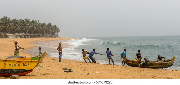 LOME, TOGO - Jan 9, 2017: Unidentified Togolese men pull a boat out of water on the coast of the Gulf of Guinea. Togo people suffer of poverty due to the bad economy