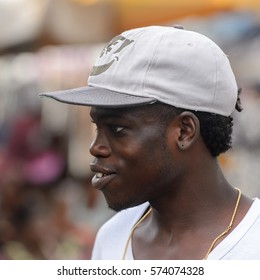 LOME, TOGO - Jan 9, 2017: Unidentified Togolese man in a white shirt and cap looks away at the Lome central market. Togo people suffer of poverty due to the bad economy