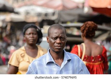 LOME, TOGO - Jan 9, 2017: Unidentified Togolese serious man in a shirt at the Lome central market. Togo people suffer of poverty due to the bad economy