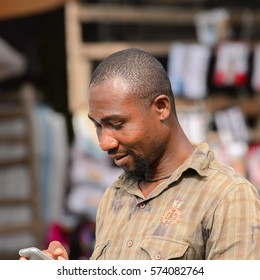 LOME, TOGO - Jan 9, 2017: Unidentified Togolese man with beard looks down in cellphone at the Lome central market. Togo people suffer of poverty due to the bad economy