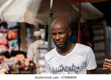 LOME, TOGO - Jan 9, 2017: Unidentified Togolese man with beard in white shirt looks down at the Lome central market. Togo people suffer of poverty due to the bad economy