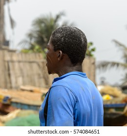 LOME, TOGO - Jan 9, 2017: Unidentified Togolese man in blue shirt  from behind on the coast of the Gulf of Guinea. Togo people suffer of poverty due to the bad economy