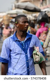 LOME, TOGO - Jan 9, 2017: Unidentified Togolese man in blue shirt listens to music at the Lome central market. Togo people suffer of poverty due to the bad economy