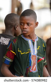 LOME, TOGO - Jan 9, 2017: Unidentified Togolese boy in green shirt looks down at the Lome fetish market. Togo people suffer of poverty due to the bad economy