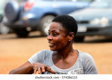 LOME, TOGO - Jan 9, 2017: Unidentified Togolese woman in grey shirt smiles at the Lome port. Togo people suffer of poverty due to the bad economy