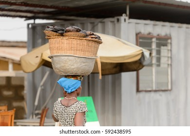 LOME, TOGO - Jan 9, 2017: Unidentified Togolese woman carries a basin on her head. Togo people suffer of poverty due to the bad economy