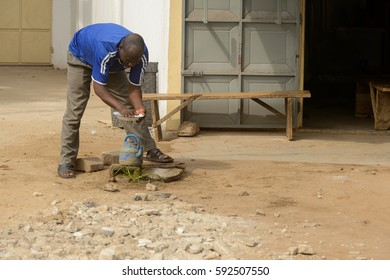 LOME, TOGO - Jan 9, 2017: Unidentified Togolese man in blue shirt bends down to wash a plate. Togo people suffer of poverty due to the bad economy