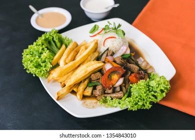 Lomo saltado with peruvian sauce and garlic sauce