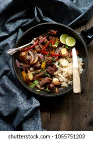 Lomo Saltado Peruvian stir fry marinated sirloin beef steak with rice in a frying pan.