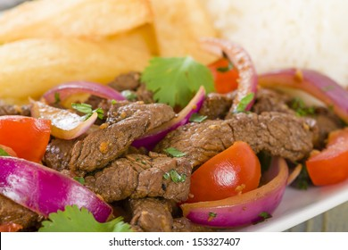Lomo Saltado - Traditional Peruvian stir-fry with beef, red onions, tomatoes and fries garnished with parsley and coriander and served with steamed rice.