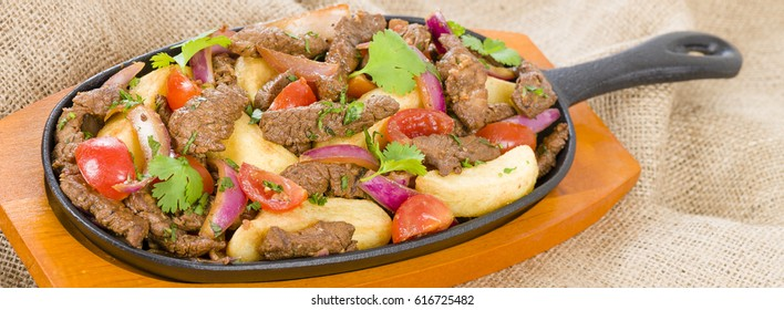 Lomo Saltado - Traditional Peruvian stir-fry with beef, red onions, tomatoes and fries garnished with parsley and coriander.