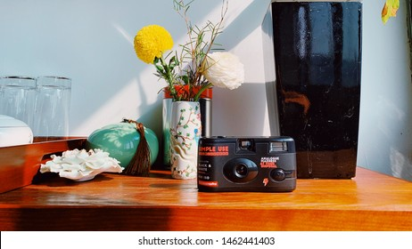 Lomography Film camera with flowers and vase decorations on wooden table with nice sunlight - 14 February 2019 Hangzhou