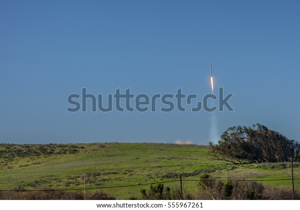 Lompoc, California, USA - January 14, 2017: Vandenberg Air Force Base where Spacex launched a Falcon 9 rocket. The rocket in the blue air one second after take off. Green grass. Fire and smoke.