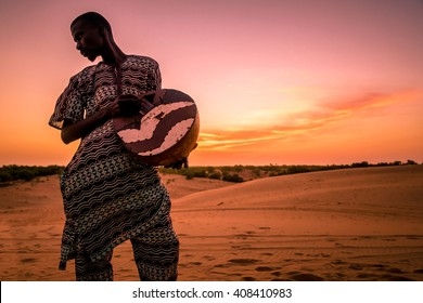 LOMPOUL/SENEGAL - NOVEMBER 12, 2013: Lonely unidentified african musician playing drum at the sunset in Lompoul desert, Senegal