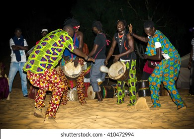 LOMPOUL/SENEGAL - NOVEMBER 12, 2013: Unidentified africans in colorful clothes play drums and dance during night in the camp at Lompoul desert, Senegal