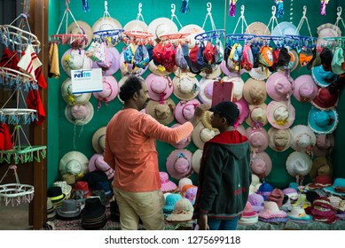 Lonavala, India - December 16 2018: A cap seller helping a kid buying a cap