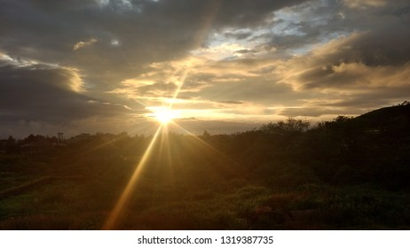 Lonavala, India - March 2018: This is a picture of the sunrise in a hillside valley near Mumbai called Lonavala and shows the sun rise up from out of the hills to break the early dawn.
