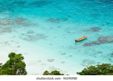 Lond tail boat anchored in a tropical bay