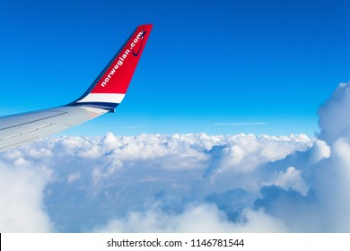 London - 7/13/16 : Fly from London Gatwick to Mallorca in Spain by Norwegian Air Shuttle. View from window on plane wing above clouds with blue sky .