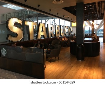 LONDON - 9 SEPTEMBER 2016: Starbucks Cafe in Heathrow Airport, London, England.  People enjoying a coffee at the airport inside a stylish Starbucks with warm lighting, soft chairs, and marquee lights.