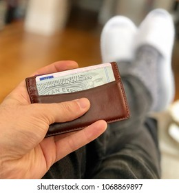 LONDON - APRIL 15, 2018: A man holds a leather wallet containing an American Express credit card in London, UK.