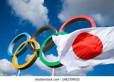 LONDON - APRIL 19, 2019: A Japanese flag flutters in the wind in front of Olympic Rings standing under bright blue sky.
