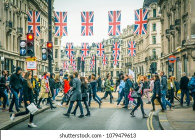 LONDON- APRIL, 2018: Crowds of shoppers on Oxford Circus with rows of British flags on Regent Street