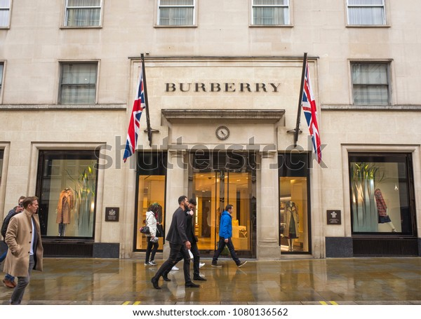 LONDON- APRIL, 2018: People walking past Burberry fashion shop on Bond Street, Mayfair in London. A high end British brand selling expensive luxury fashion items.