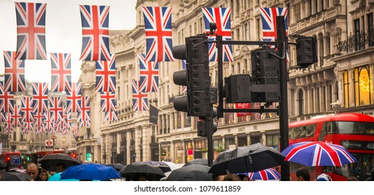 LONDON- APRIL, 2018: View of Regent Street in London's west end with many shoppers with umbrellas- a famous London landmark and popular shopping street