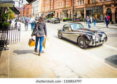 LONDON- APRIL, 2018: A woman carrying shopping bags on Mount Street, an upmarket red brick shopping high street in Mayfair