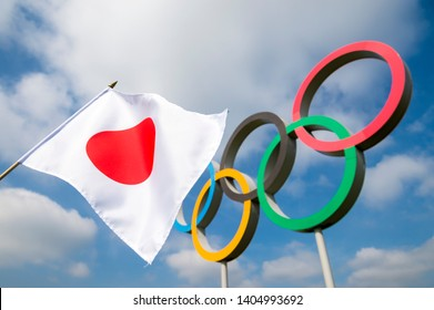 LONDON - APRIL, 2019: A Japanese flag flutters in the wind in front of Olympic Rings standing under bright blue sky.