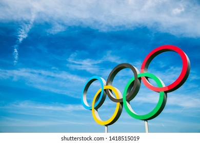 LONDON - APRIL, 2019: A large set of Olympic Rings stand under bright blue sky.