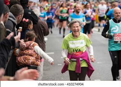 LONDON - April 24 2016. The London Marathon. Elderly lady enjoying the atmosphere whilst running the marathon.