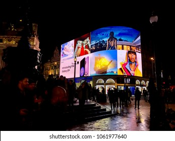LONDON - APRIL 4, 2018: Tourists lit up at night by bright advertising illumination screens in Piccadilly Circus, Westminster, London, UK.