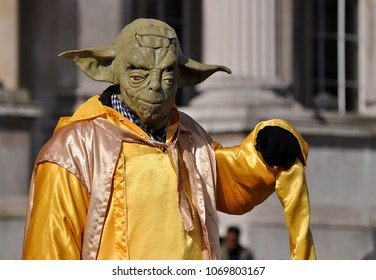 LONDON - APRIL 5, 2018. A street performer, dressed as the Star Wars character Yoda, entertains visitors to Trafalgar Square, a popular tourist venue in central London, UK.